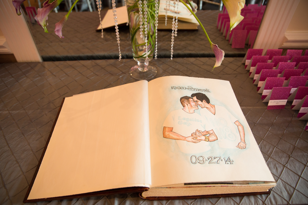 As guests entered the ceremony, they were asked to stop and sign the couple's guest book, which featured hand drawn images from throughout their relationship by The Girl Who Drew You.   Destination Wedding Planner Andrea Eppolito  |  Photo by Antonio Abrego | Gay Weddings