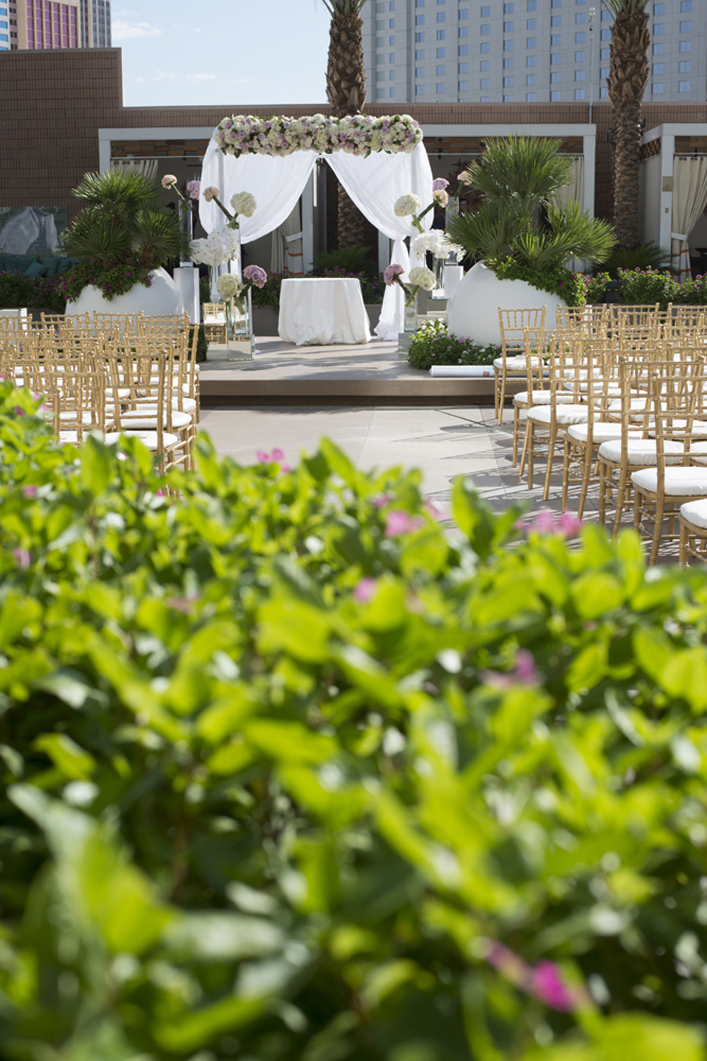 With the cabanas in the background, guests entered to find gold chiavari chairs lining the side of the pool deck.   Las Vegas Wedding at   Mandarin Oriental   |  Photo by  Altf Photography   |  Floral and Decor by  Naakiti Floral   |  Las Vegas Wedding Planner  Andrea Eppolito