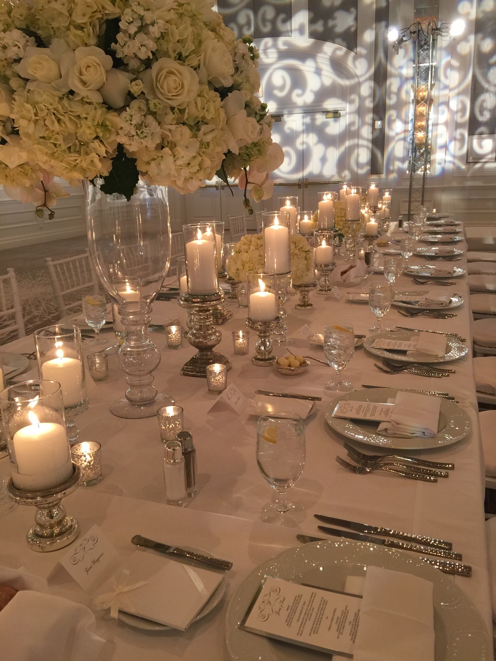 Guests were set at long banquet tables dressed in white linens with hundreds of candles at varying heights.  Small, low floral were placed throughout to soften the space, and a cluster of chandelier hung above a white dance floor.  This room  was magnificent!  Photo by  Andrea Eppolito.