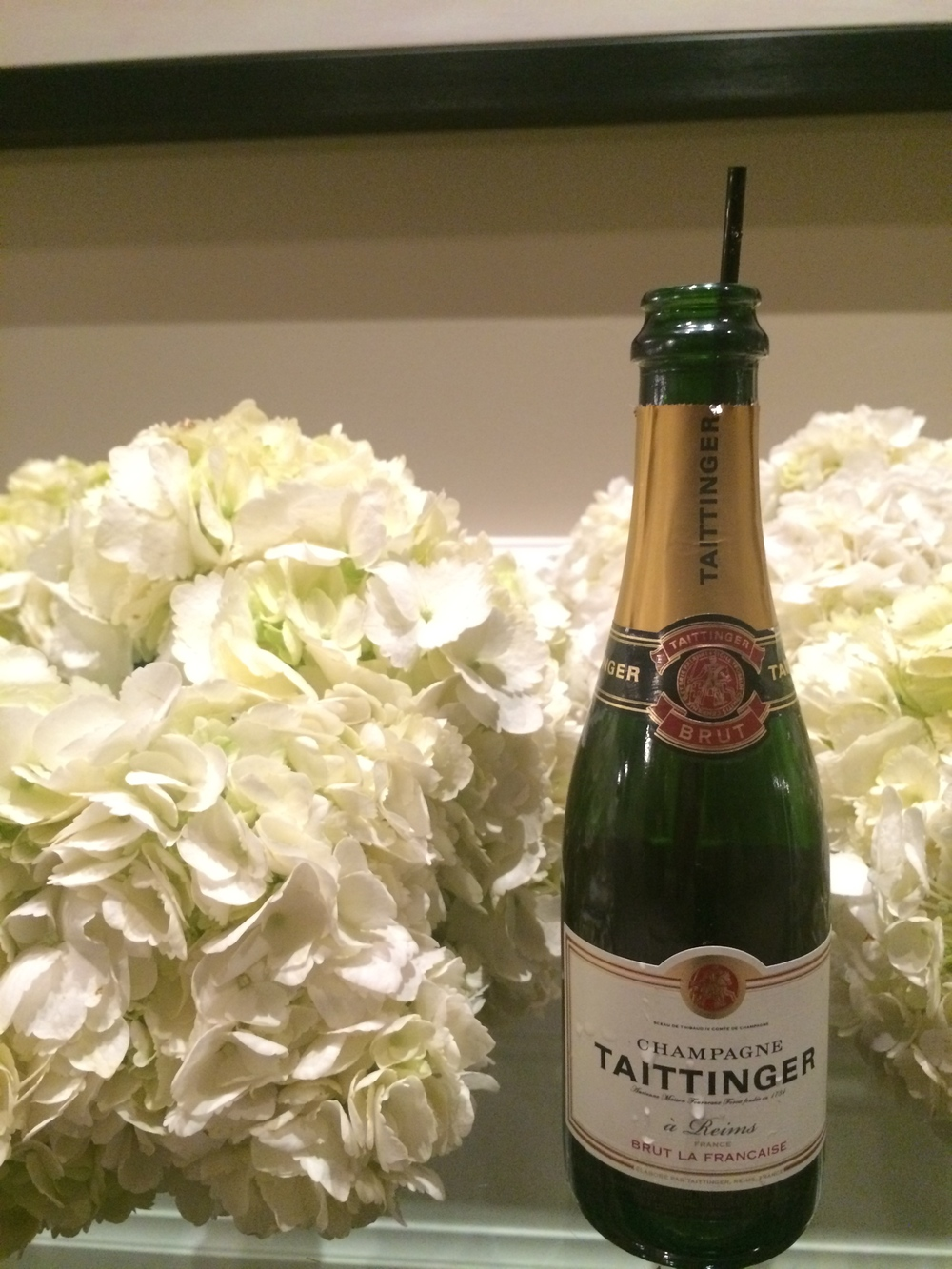 A toast!  As they departed for the fire work display, each guest was presented with an individual bottle of Taittinger Champagne and a bouquet of Hydrangea, the bride's favorite.   Photo by   Andrea Eppolito.