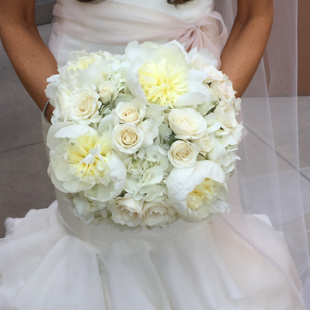 The bride carried a bouquet of ivory and blush roses, hydrangea, and peonies.