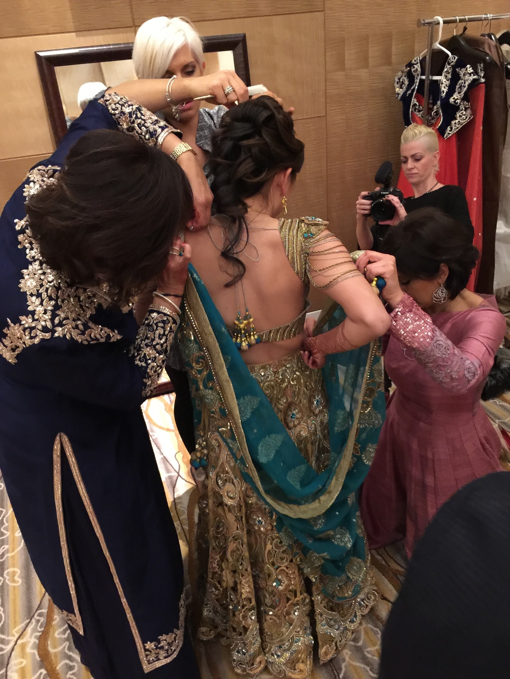 It takes a village....Literally!  The bride's hair and make up was transformed by Make Up in the 702 as her sister-in-laws dressed her.