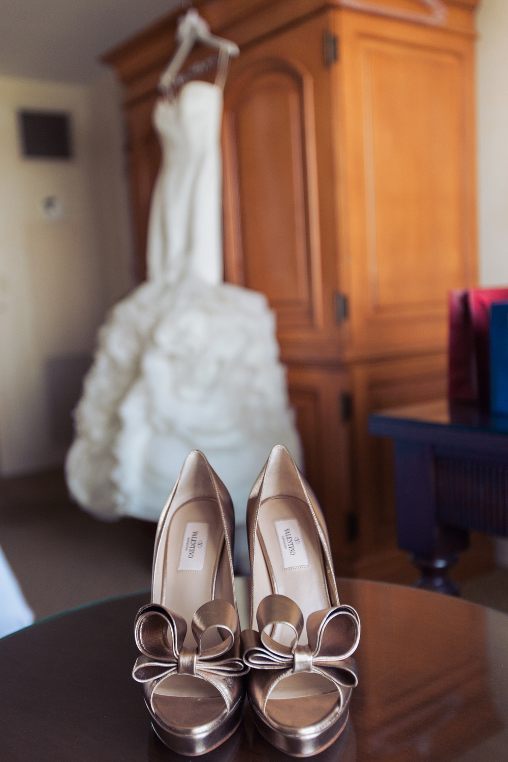 The bride's Rivini wedding gown hung in the back while her golden bronze Valentino BOW shoes took center stage.      Las Vegas Wedding Planner Andrea Eppolito  |  Wedding at Lake Las Vegas  | White and Blu  sh and Grey Wedding | Luxury Wedding Las Vegas