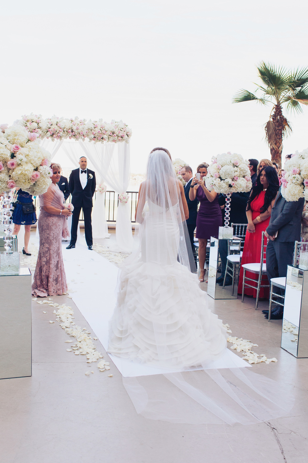 The bride walked half way down the aisle on her own before meeting her mother, who gave her away at the end.      Las Vegas Wedding Planner Andrea Eppolito  |  Wedding at Lake Las Vegas  | White and Blu  sh and Grey Wedding | Luxury Wedding Las Vegas