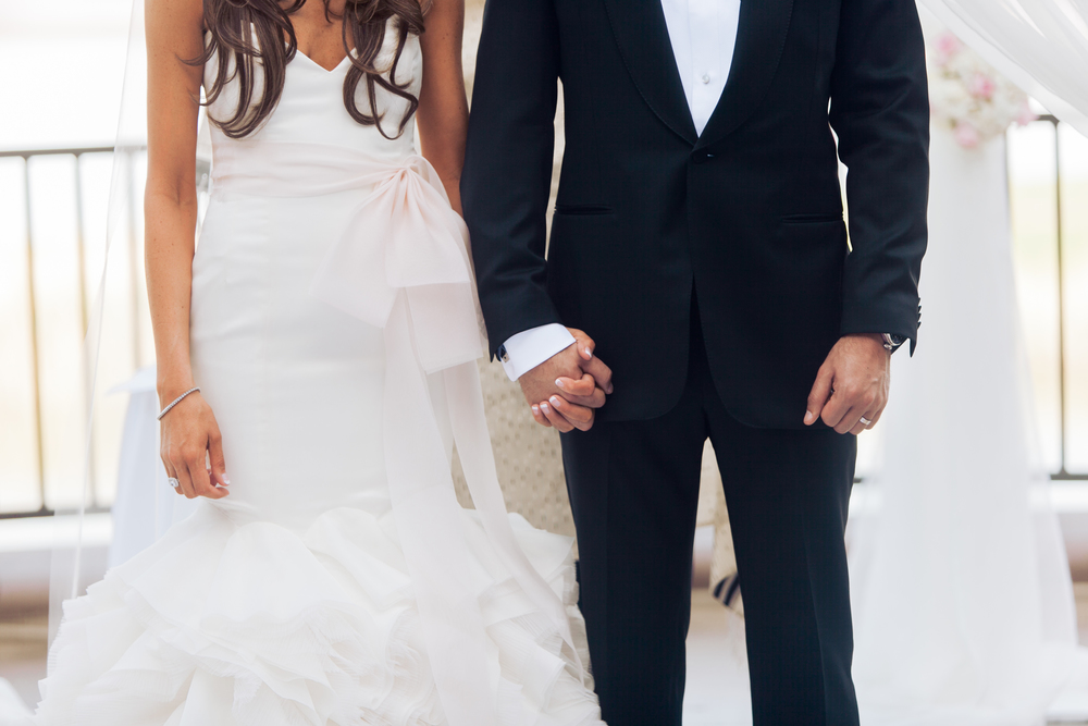 The bride and groom held hands as they were presented to their guests and blessed.      Las Vegas Wedding Planner Andrea Eppolito  |  Wedding at Lake Las Vegas  | White and Blu  sh and Grey Wedding | Luxury Wedding Las Vegas