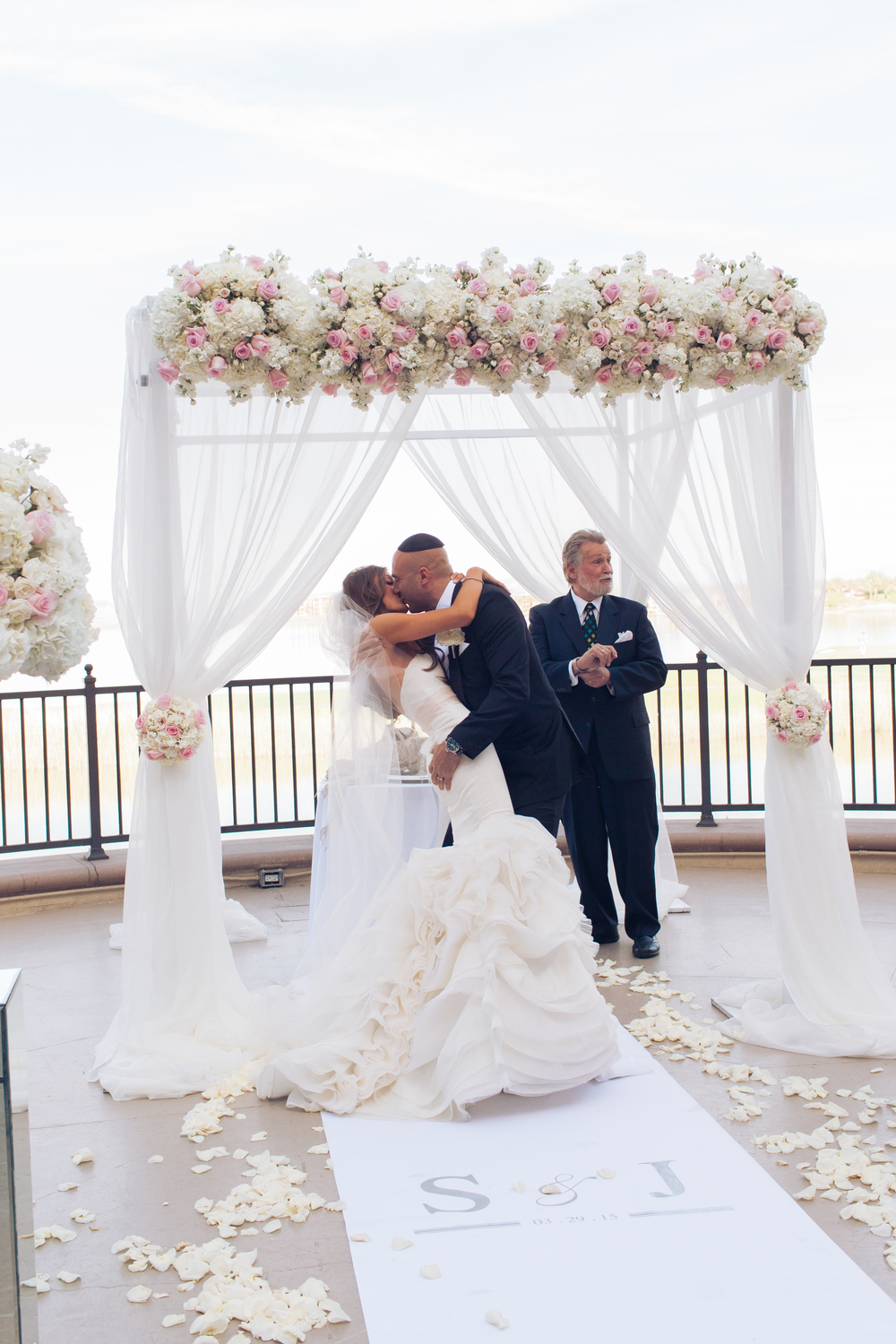 The couple's dramatic first kiss had the groom dipping the bride in front of their guests and Rabbi Mel Hecht.      Las Vegas Wedding Planner Andrea Eppolito  |  Wedding at Lake Las Vegas  | White and Blu  sh and Grey Wedding | Luxury Wedding Las Vegas