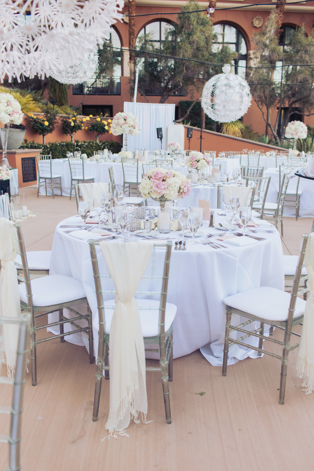 The bridal party sat at special, dedicated round tables dressed with White Duping linens topped with mirrored table runners, high and low white and blush centerpieces, and scattered candles.  Lucite Chiavari Chairs with ivory cushions surrounded the tables, and pashminas were placed for the ladies if they felt a chill.   Las Vegas Wedding Planner Andrea Eppolito  |  Wedding at Lake Las Vegas  | White and Blu  sh and Grey Wedding