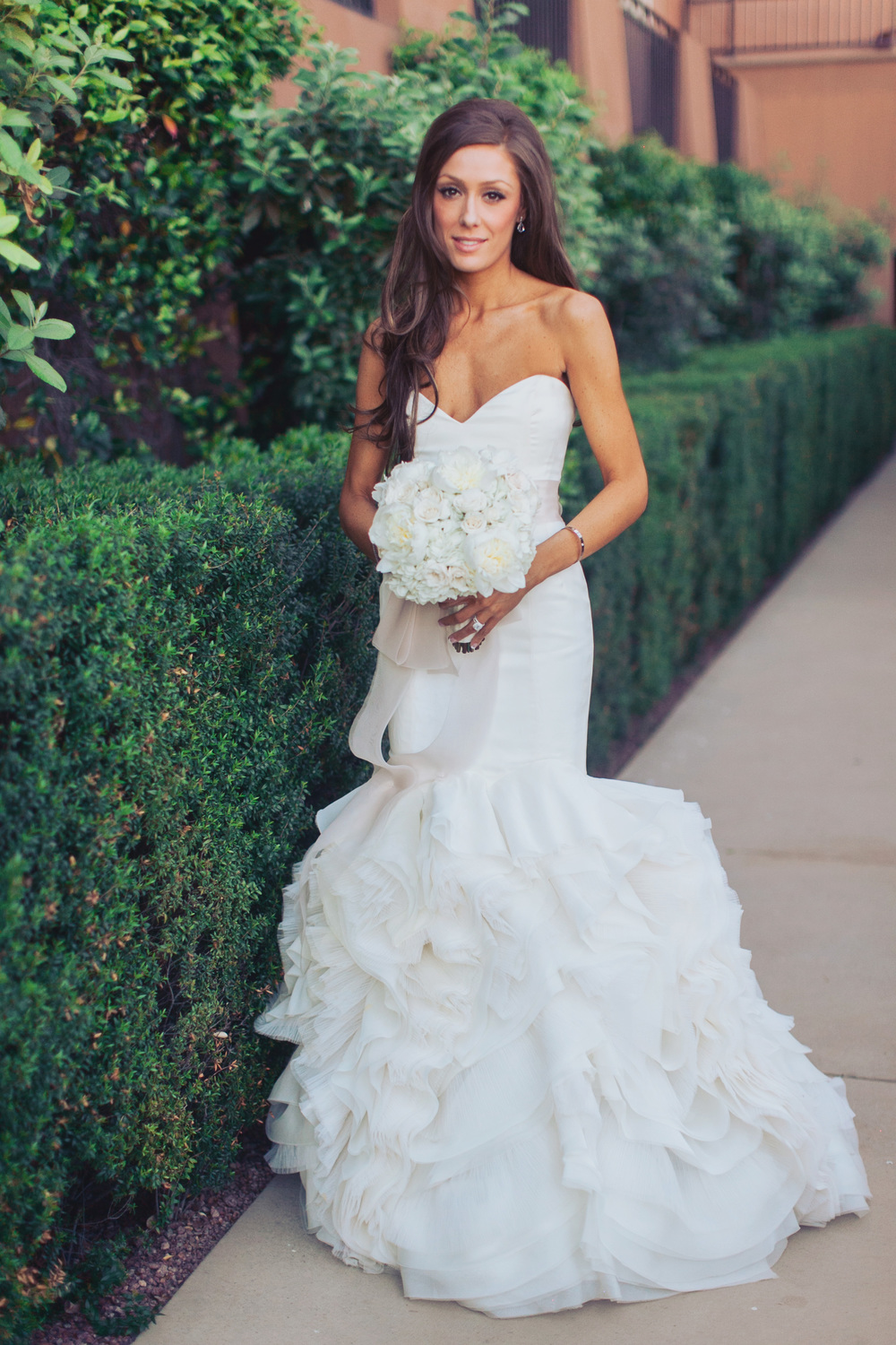 The bride wore an ivory gown by Rivini accented with a blush bow.  her Cartier LOVE bangle was a gorgeous compliment to her Tiffany & Co engagement ring and wedding band.      Las Vegas Wedding Planner Andrea Eppolito  |  Wedding at Lake Las Vegas  | White and Blu  sh and Grey Wedding | Luxury Wedding Las Vegas