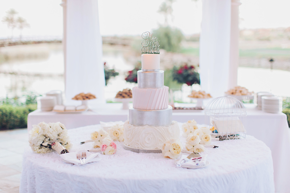 The ivory, blush, and platinum wedding cake was set in front of a sweets table.  Cake by Peridot Sweets.   Stephanie Di Lallo married   Justin Oliver at a water front   wedding at The Westin Lake Las Vegas.       Las Vegas Wedding Planner Andrea Eppolito  |  Wedding at Lake Las Vegas  | White and Blu  sh and Grey Wedding | Luxury Wedding Las Vegas