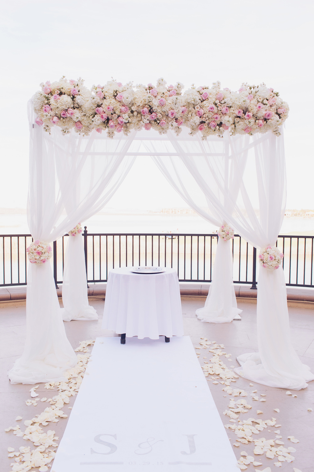 For the lakeside ceremony we dressed a chuppah in flowing ivory fabric topped with ivory and pale pink roses.  Matching topiaries lined the aisle.       Las Vegas Wedding Planner Andrea Eppolito  |  Wedding at Lake Las Vegas  | White and Blu  sh and Grey Wedding | Luxury Wedding Las Vegas