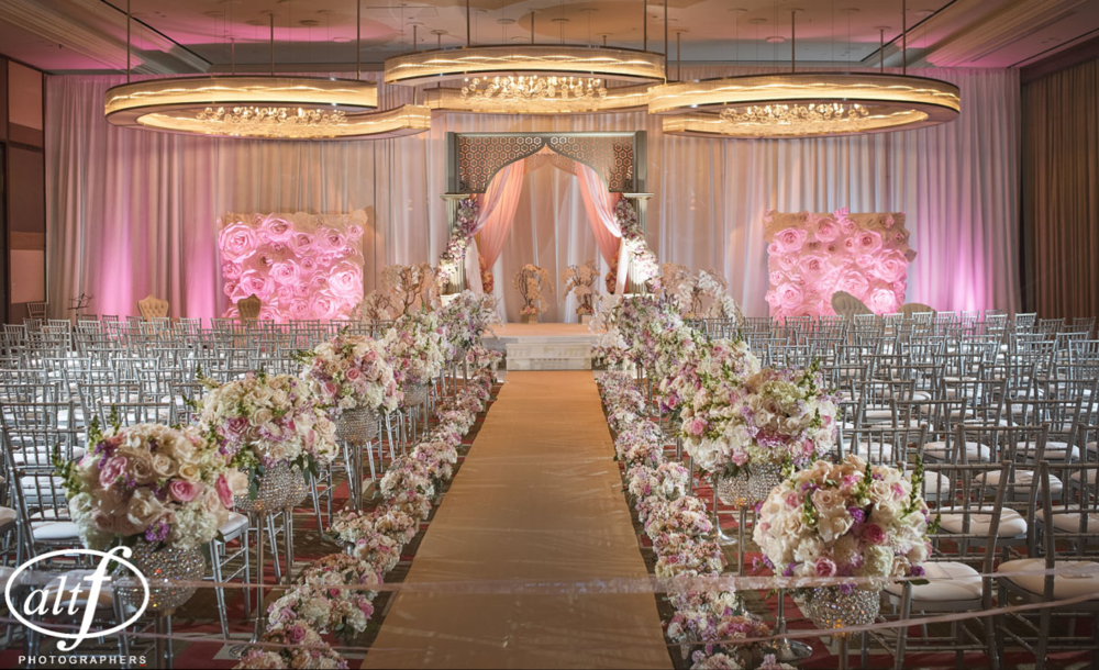 A luxury mandap made of gold laser cut wood, blush drapes, and roses in shades of cream and pink.  The aisle was lined with a gold aisle runner, and finished with crystal goblets filled with hydrangea, roses, and ranunculus.  Indian Wedding at the Mandarin Oriental.  Las Vegas Wedding Planner Andrea Eppolito.  Photo by Altf.