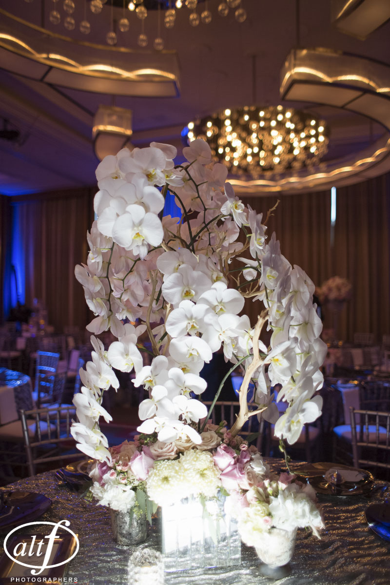 Orchid and Rose Center piece with a mirrored base.  Luxury wedding reception featuring orchid trees, roses, silver table cloths, and chiavari chairs.  Blue lighting.  Las Vegas Wedding Planner Andrea Eppolito.  Photo by Altf.  Florals, Decor, and Entertainment by DBD Vegas.