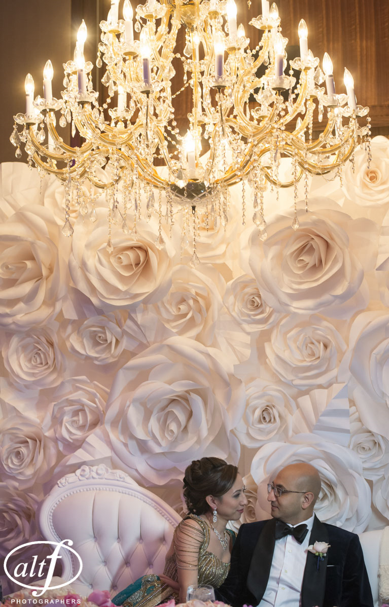 Bridal portraits in front of their paper flower wall at the Mandarin Oriental.  Luxury Indian Las Vegas Wedding Planner Andrea Eppolito.  Photo by Altf.  Florals, Decor, and Entertainment by DBD Vegas.
