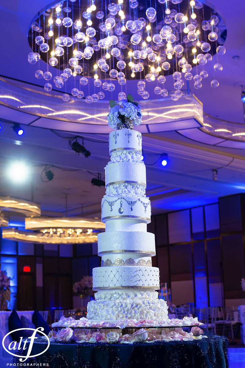 This 12 tiered wedding cake included 6 layers of cake and six lifts.  Decorated with white iridescent fondant and finished with jewels and gold bands, this was the showpiece of the wedding.   Indian Wedding at the Mandarin Oriental.  Luxury Las Vegas Wedding Planner Andrea Eppolito.  Photo by Altf Photography.  Floral, Decor, and Entertainment by DBD Las Vegas.