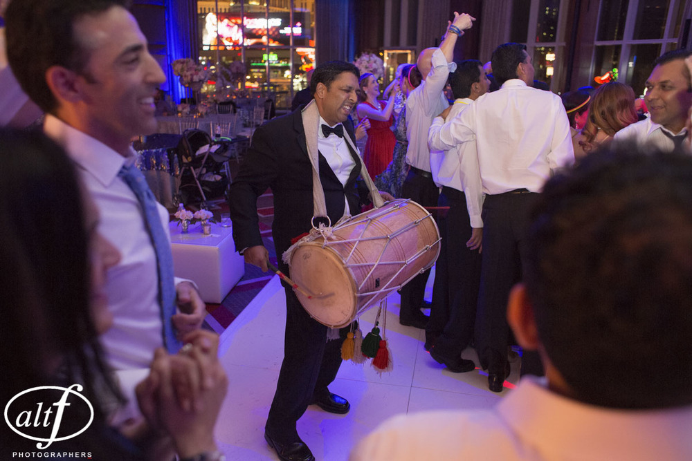Guests stole the dhol drum and passed it around, playing joyously on the dance floor.  Indian Wedding at the Mandarin Oriental.  Luxury Las Vegas Wedding Planner Andrea Eppolito.  Photo by Altf Photography.