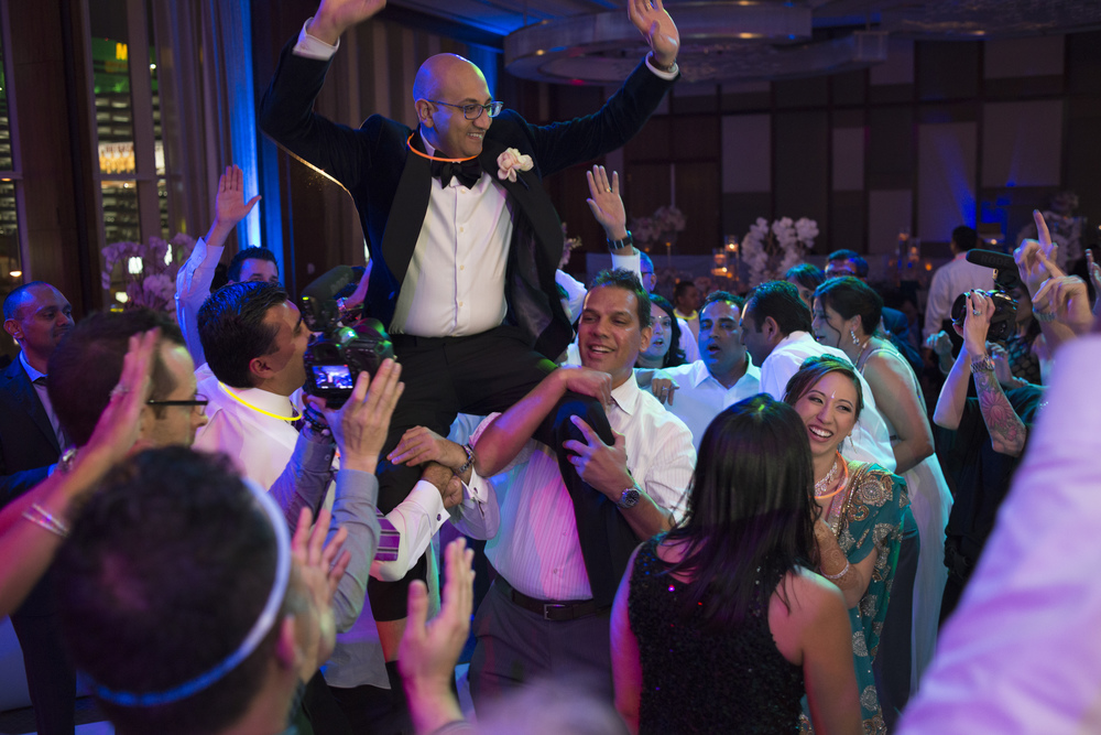 The groom was hoisted in the air on the dance floor.  Indian Wedding at the Mandarin Oriental.  Luxury Las Vegas Wedding Planner Andrea Eppolito.  Photo by Altf Photography.