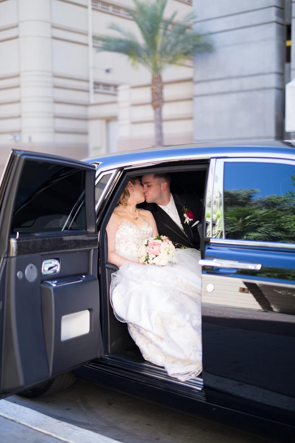 Bride and groom kissing in a rolls royce on their wedding day.  Las Vegas Wedding Planner Andrea Eppolito  |  Wedding at The Venetian Las Vegas  |  Florals and Decor by Naakiti Floral  |  Photos by Meg Ruth
