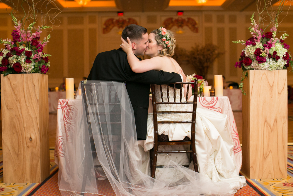 The bride and groom kiss at their sweetheart table.  Las Vegas Wedding Planner Andrea Eppolito  |  Wedding at The Venetian Las Vegas  |  Florals and Decor by Naakiti Floral  |  Photos by Meg Ruth