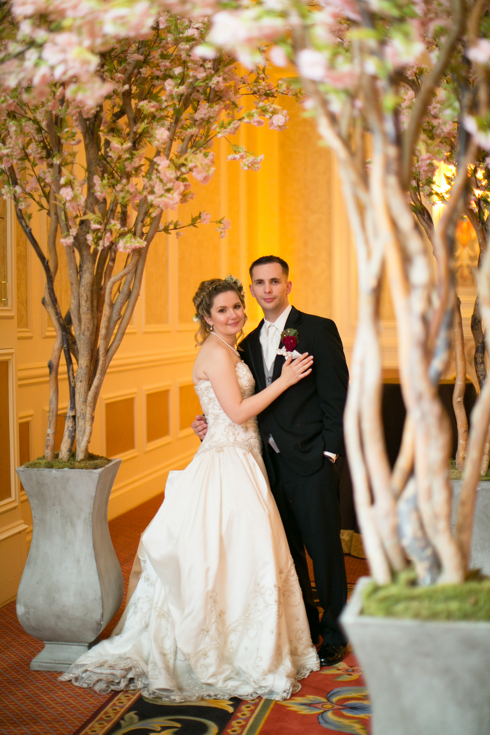The bride and groom under cherry blossom trees.   Las Vegas Wedding Planner Andrea Eppolito  |  Wedding at The Venetian Las Vegas  |  Florals and Decor by Naakiti Floral  |  Photos by Meg Ruth