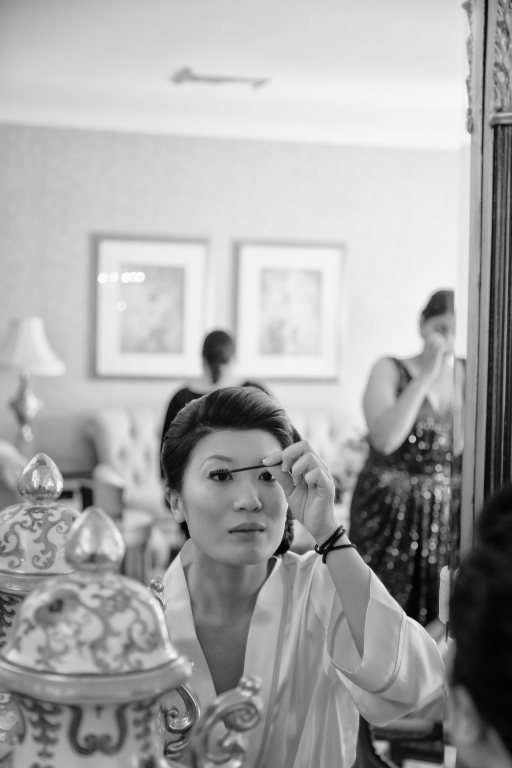 The bride checks her look and applies one last coat of mascara.  Vendor Credit:  Las Vegas Wedding Planner Andrea Eppolito | Photo: Adam Frazier Photography | Decor: Naakiti Floral | Beauty: Make Up in the 702