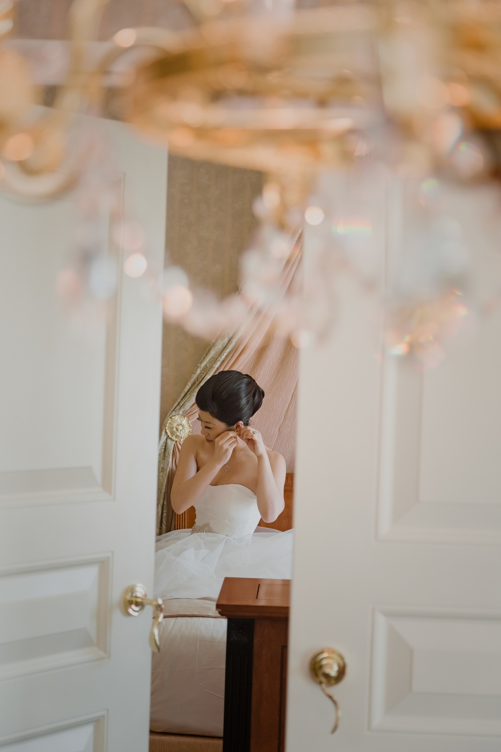 Putting on the wedding jewelry and finishing touches.  Vendor Credit:  Venue: Paris Hotel Las Vegas and Chateau | Las Vegas Wedding Planner Andrea Eppolito | Photo: Adam Frazier Photography | Decor: Naakiti Floral | Beauty: Make Up in the 702