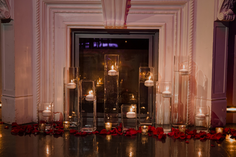 Candles at the front of the fireplace. Vendor Credit:  Venue: Paris Hotel Las Vegas and Chateau | Las Vegas Wedding Planner Andrea Eppolito | Photo: Adam Frazier Photography | Decor: Naakiti Floral | Beauty: Make Up in the 702