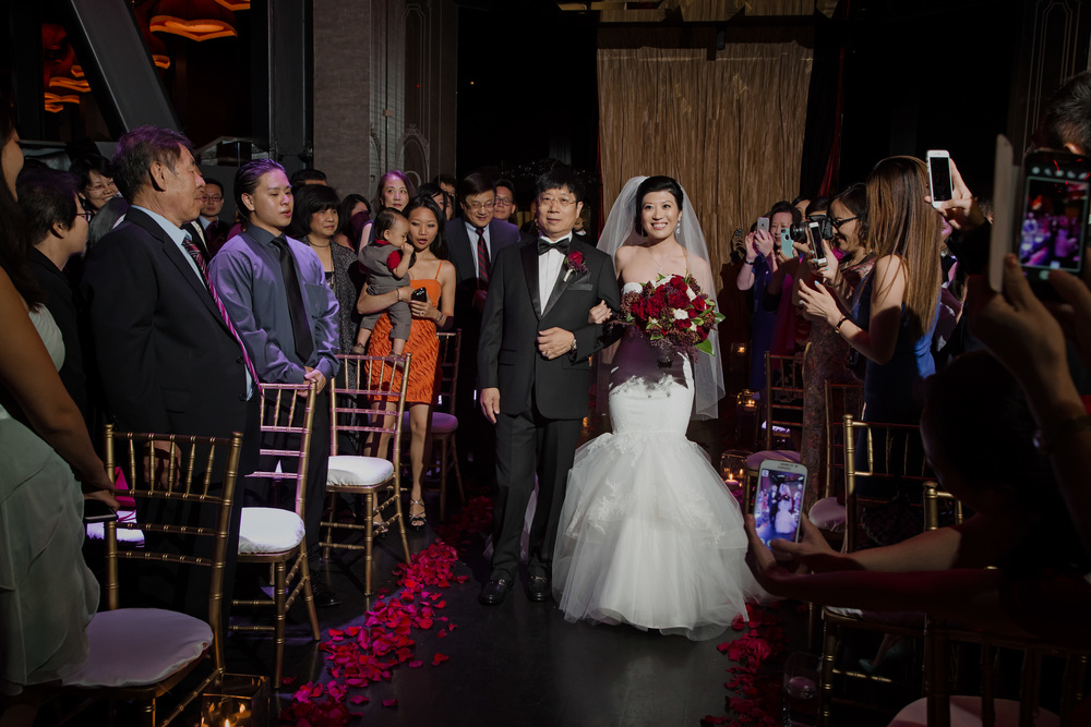 The bride being given away from her father.  Vendor Credit:  Venue: Paris Hotel Las Vegas and Chateau | Las Vegas Wedding Planner Andrea Eppolito | Photo: Adam Frazier Photography | Decor: Naakiti Floral | Beauty: Make Up in the 702