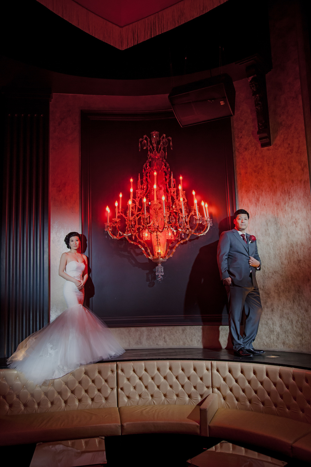 The bride wore a strapless mermaid style satin and tulle gown with beaded belt by Winnie Couture while the groom wore a grey Hugo Boss Suit.  The red chandelier was a perfect prop for modern wedding portraits.  Vendor Credit:  Venue: Paris Hotel Las Vegas and Chateau | Las Vegas Wedding Planner Andrea Eppolito | Photo: Adam Frazier Photography | Decor: Naakiti Floral | Beauty: Make Up in the 702