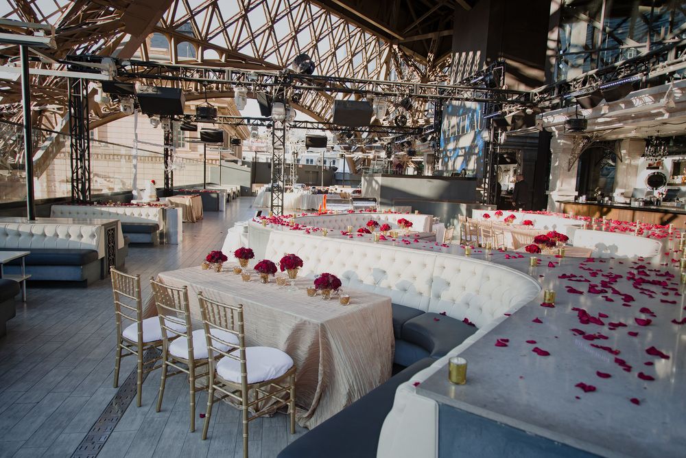 The rooftop of Chateau Nightclub was dressed with gold sequence linens, gold taffeta linens, red rose petals, and golden votives.  Vendor Credit:  Venue: Paris Hotel Las Vegas and Chateau | Las Vegas Wedding Planner Andrea Eppolito | Photo: Adam Frazier Photography | Decor: Naakiti Floral
