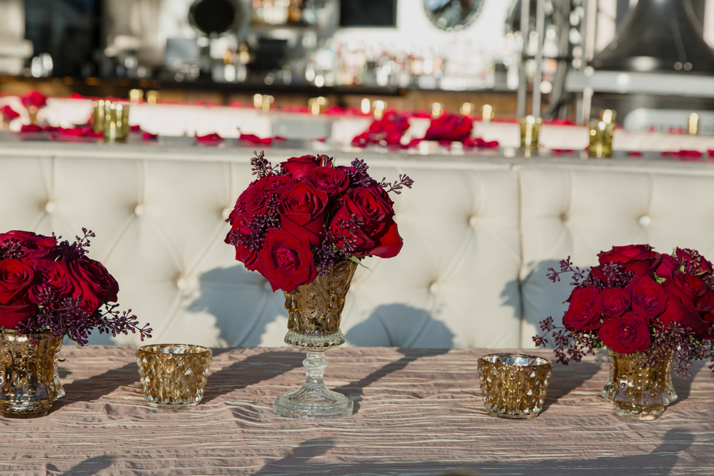 Dark Red Roses in Gold Vases served as centerpieces.  V  endor Credit:  Venue: Paris Hotel Las Vegas and Chateau | Las Vegas Wedding Planner Andrea Eppolito | Photo: Adam Frazier Photography | Decor: Naakiti Floral | Beauty: Make Up in the 702