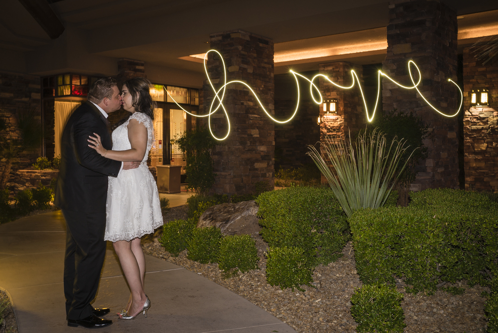 Writing with sparklers at a wedding.   Las Vegas Wedding Planner Andrea Eppolito planned this wedding at Red Rock Country Club. By Dzign handled the decor shot by wedding photographer Ella Gagiano.