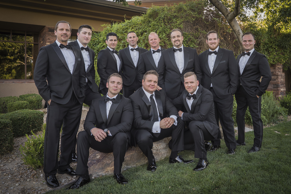 A large bridal party with 10 groomsmen in Hugo Boss tuxedos.  Las Vegas Wedding Planner Andrea Eppolito designed this luxury wedding at Red Rock Country Club. By Dzign handled the decor shot by wedding photographer Ella Gagiano.