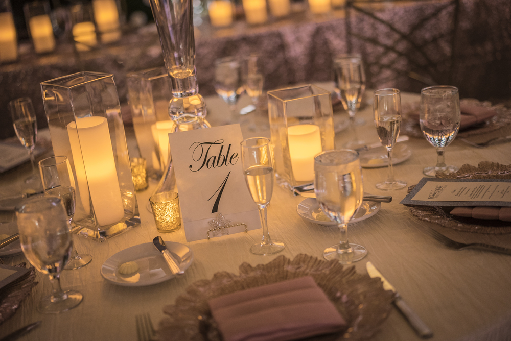 Printed Table Numbers sit on gold stands.    Las Vegas Wedding Planner Andrea Eppolito designed this luxury wedding at Red Rock Country Club. By Dzign handled the decor shot by wedding photographer Ella Gagiano.