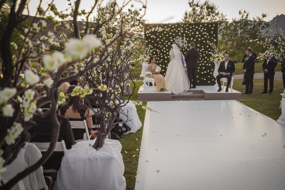 Large trees lined the aisle of the ceremony, complimenting the white stage and the garden inspired wedding.  Las Vegas Wedding Planner Andrea Eppolito designed this luxury wedding at Red Rock Country Club. By Dzign handled the decor shot by wedding photographer Ella Gagiano.