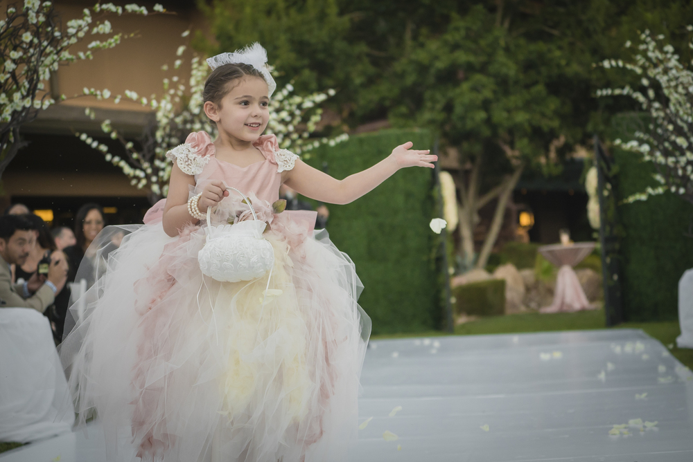 Tulle and feather flower girl dress for walking down the aisle.  Las Vegas Wedding Planner Andrea Eppolito designed this luxury wedding at Red Rock Country Club. By Dzign handled the decor shot by wedding photographer Ella Gagiano.