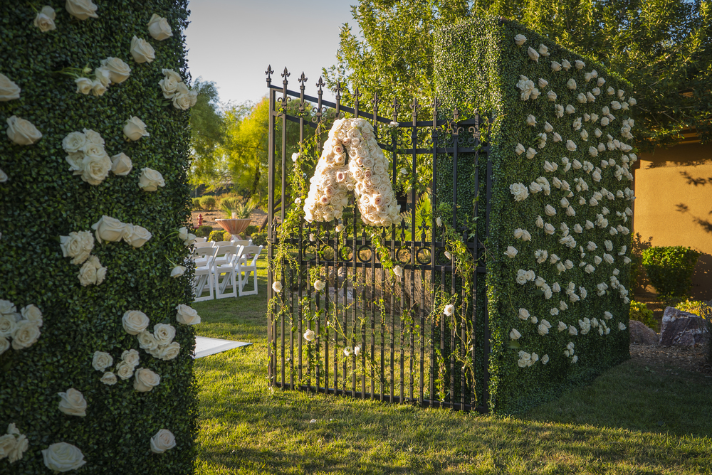 Gate at a wedding ceremony with the couple's monogram in flowers.  Las Vegas Wedding Planner Andrea Eppolito designed this luxury wedding at Red Rock Country Club. By Dzign handled the decor shot by wedding photographer Ella Gagiano.