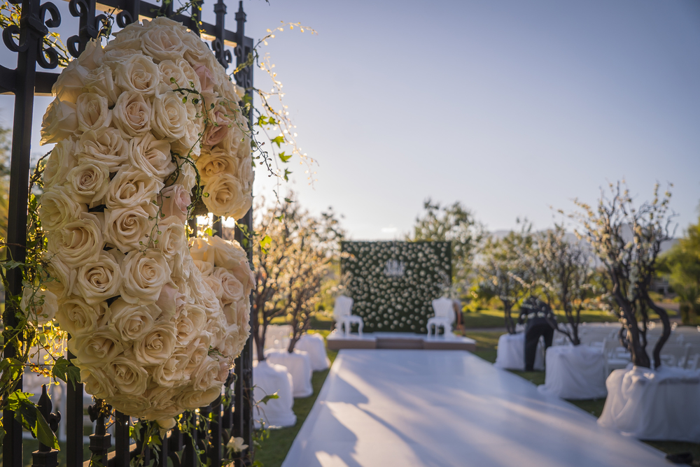 Garden inspired wedding with wrought iron gates, green hedges, and a white hard aisle.  Las Vegas Wedding Planner Andrea Eppolito designed this luxury wedding at Red Rock Country Club. By Dzign handled the decor shot by wedding photographer Ella Gagiano.