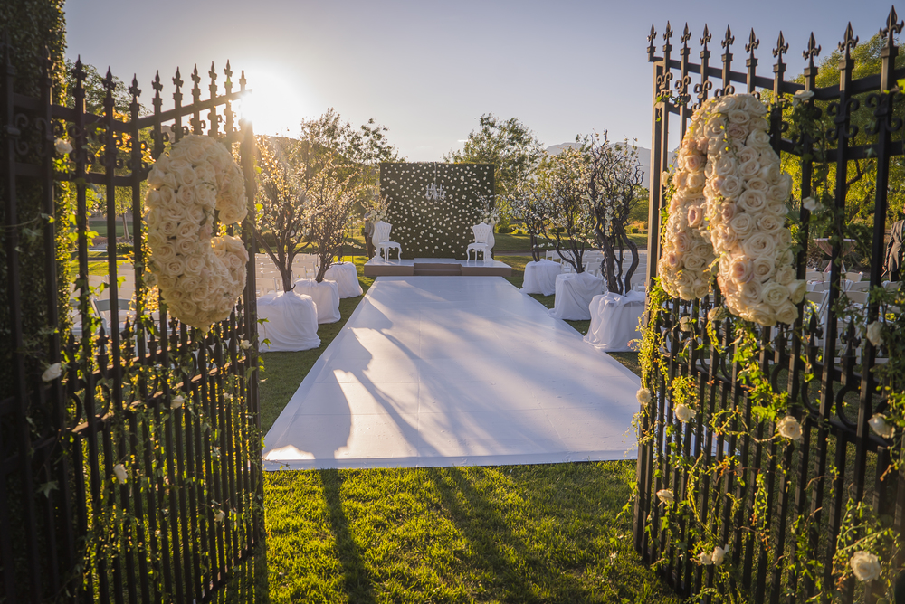 Gate at a wedding ceremony with the couple's monogram in flowers.Garden inspired wedding with wrought iron gates, green hedges, and a white hard aisle.  Las Vegas Wedding Planner Andrea Eppolito designed this luxury wedding at Red Rock Country Club. By Dzign handled the decor shot by wedding photographer Ella Gagiano.