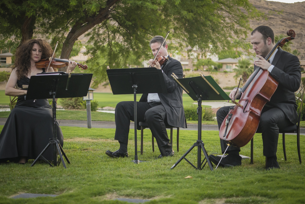 Live string trio playing at an outdoor wedding.  Las Vegas Wedding Planner Andrea Eppolito designed this luxury wedding at Red Rock Country Club. By Dzign handled the decor shot by wedding photographer Ella Gagiano.