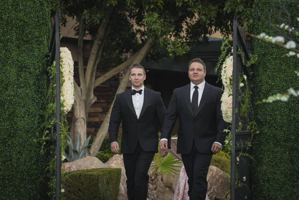 Groom enters ceremony with his best man through monogrammed gates.   Las Vegas Wedding Planner Andrea Eppolito designed this luxury wedding at Red Rock Country Club. By Dzign handled the decor shot by wedding photographer Ella Gagiano.