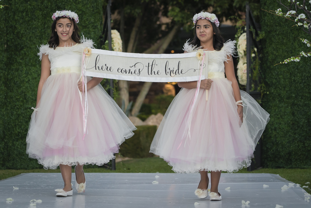 """Here Comes the Bride"" sign carried by flower girls in tulle.   Las Vegas Wedding Planner Andrea Eppolito designed this luxury wedding at Red Rock Country Club. By Dzign handled the decor shot by wedding photographer Ella Gagiano."