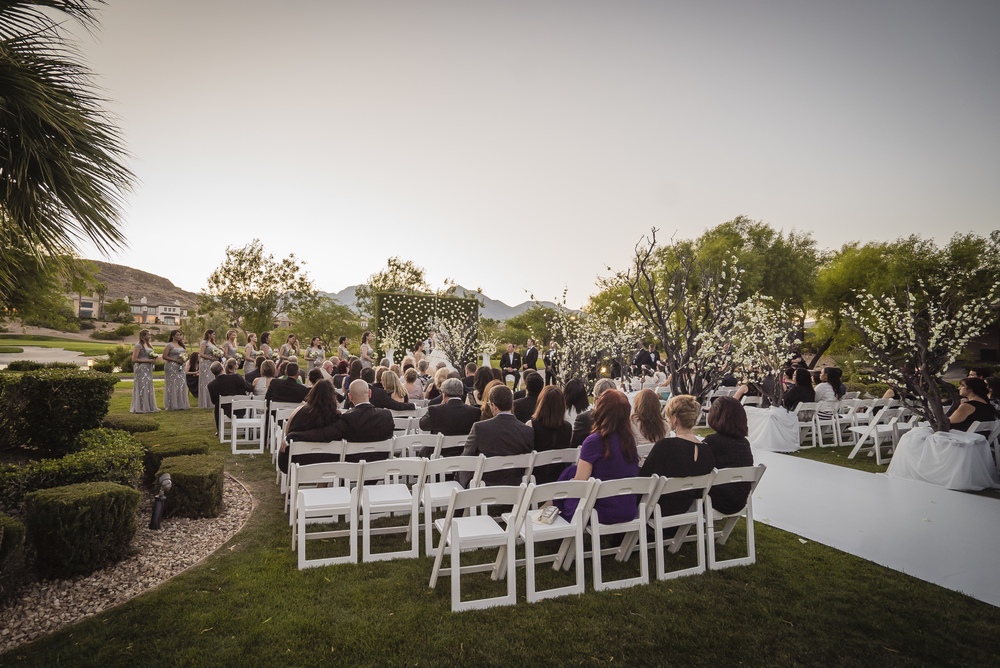 Garden style wedding ceremony at Red Rock Country Club.  Flower walls and hedges and cherry blossom trees added privacy.  Las Vegas Wedding Planner Andrea Eppolito designed this luxury wedding at Red Rock Country Club. By Dzign handled the decor shot by wedding photographer Ella Gagiano.
