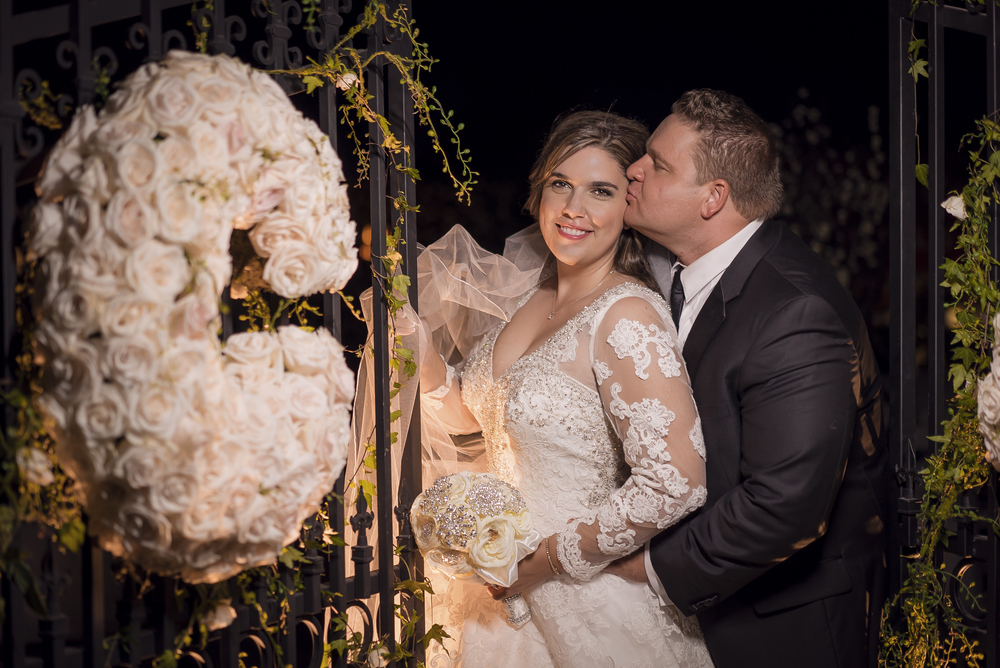 Bride and groom photographed at night between two two gates.  Las Vegas Wedding Planner Andrea Eppolito designed this luxury wedding at Red Rock Country Club. By Dzign handled the decor shot by wedding photographer Ella Gagiano.
