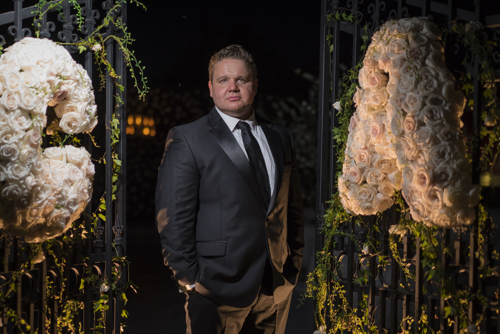 Photo of groom between two gates taken at night.   Las Vegas Wedding Planner Andrea Eppolito designed this luxury wedding at Red Rock Country Club. By Dzign handled the decor shot by wedding photographer Ella Gagiano.