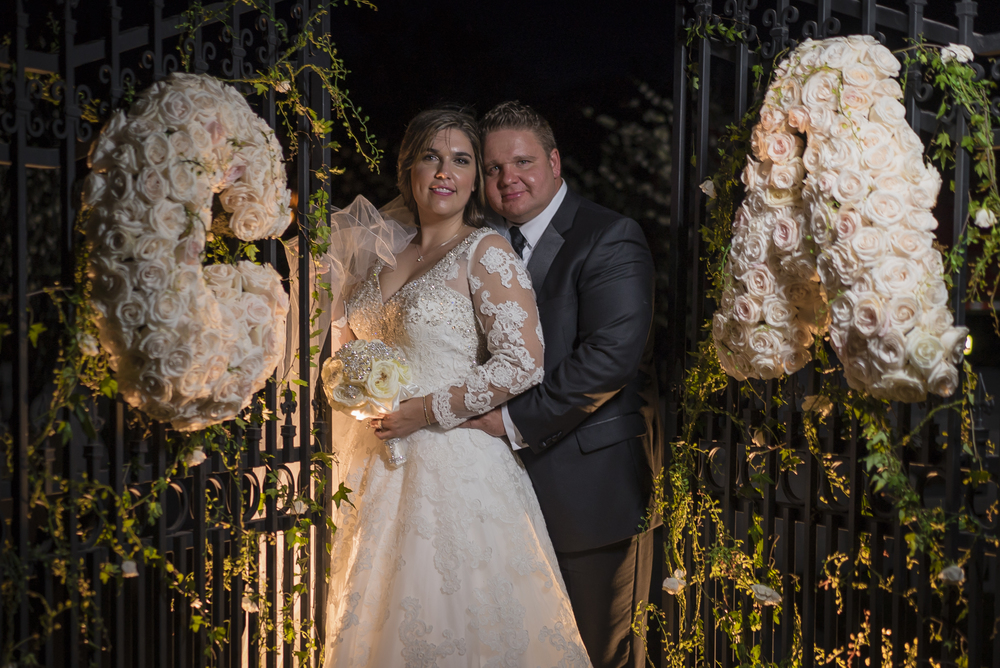 Bride and Groom photographed between gates with floral monograms.  Initials made of cream roses.   Las Vegas Wedding Planner Andrea Eppolito designed this luxury wedding at Red Rock Country Club. By Dzign handled the decor shot by wedding photographer Ella Gagiano.