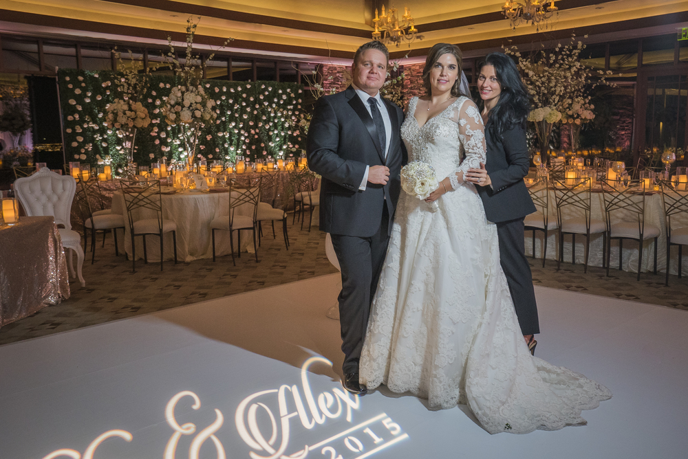 Las Vegas Wedding Planner Andrea Eppolito poses with a bride and groom at their luxury wedding.  Las Vegas Wedding Planner Andrea Eppolito designed this luxury wedding at Red Rock Country Club. By Dzign handled the decor shot by wedding photographer Ella Gagiano.
