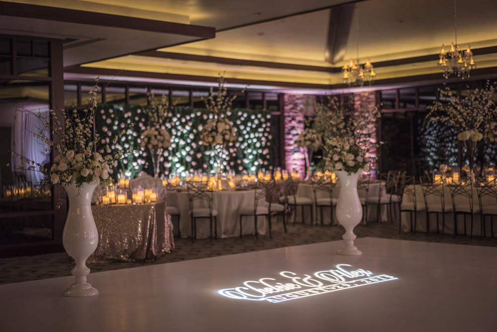 A flower wall sits behind the head table.  The white dance floor has a gobo light monogram.  Las Vegas Wedding Planner Andrea Eppolito designed this luxury wedding at Red Rock Country Club. By Dzign handled the decor shot by wedding photographer Ella Gagiano.
