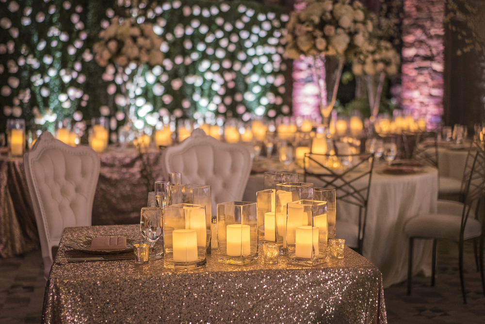 The sweetheart table had fancy white chairs and blush sequence linen.  Las Vegas Wedding Planner Andrea Eppolito designed this luxury wedding at Red Rock Country Club. By Dzign handled the decor shot by wedding photographer Ella Gagiano.