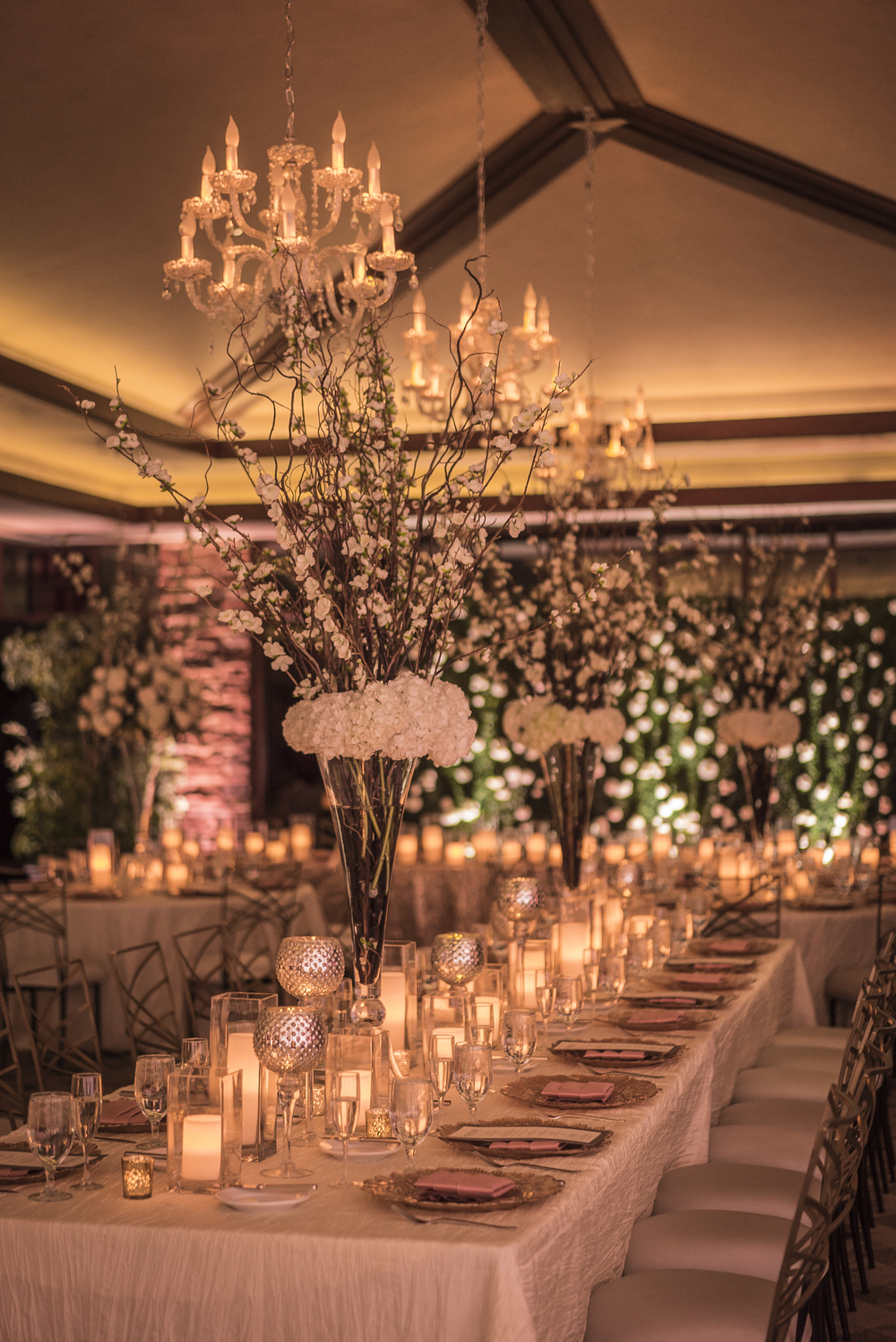 Long tables were topped with golden candles and tall centerpieces with cherry blossoms.   Las Vegas Wedding Planner Andrea Eppolito designed this luxury wedding at Red Rock Country Club. By Dzign handled the decor shot by wedding photographer Ella Gagiano.