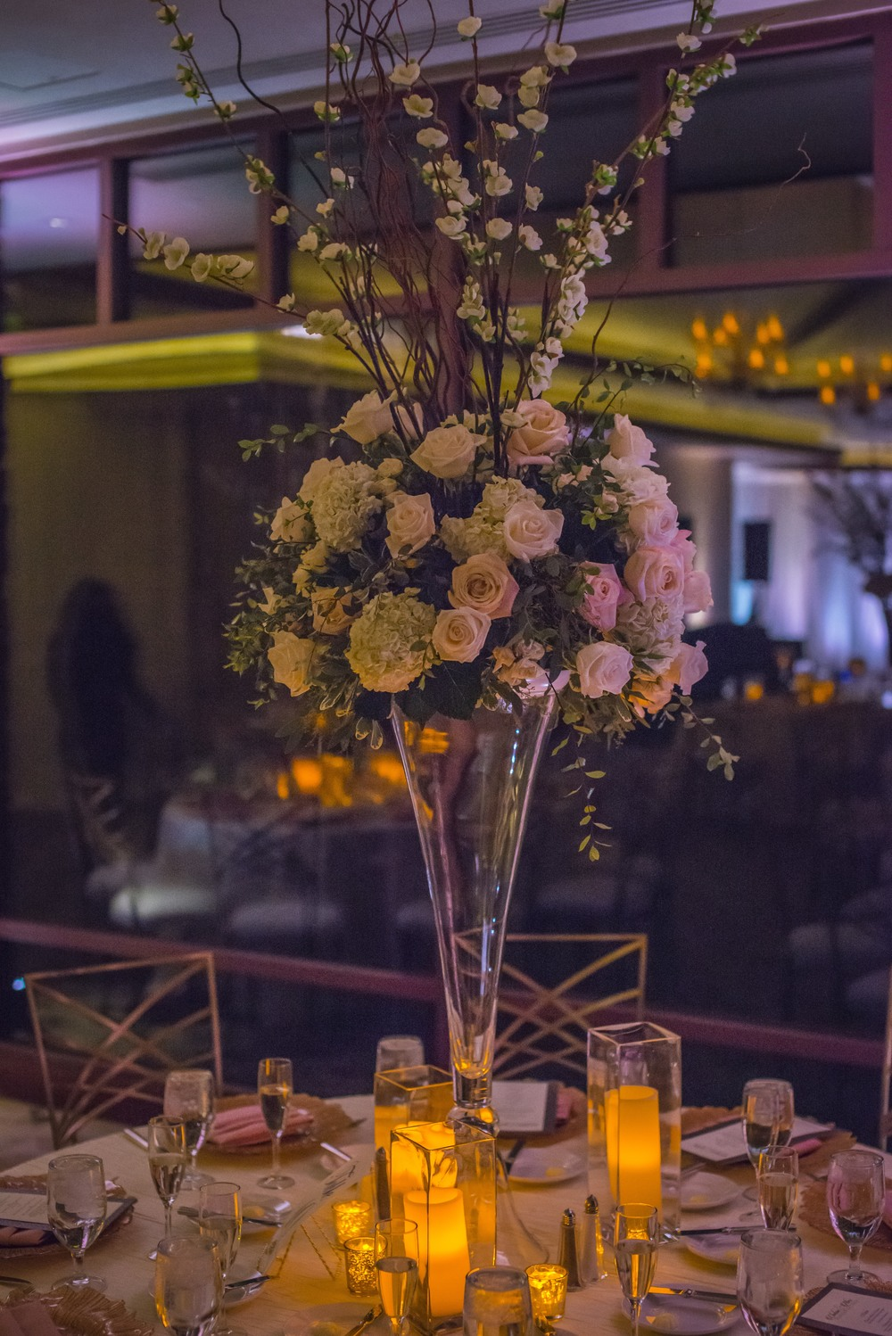 Tall centerpieces made of roses and hydrangea were set on the round tables.   Las Vegas Wedding Planner Andrea Eppolito designed this luxury wedding at Red Rock Country Club. By Dzign handled the decor shot by wedding photographer Ella Gagiano.